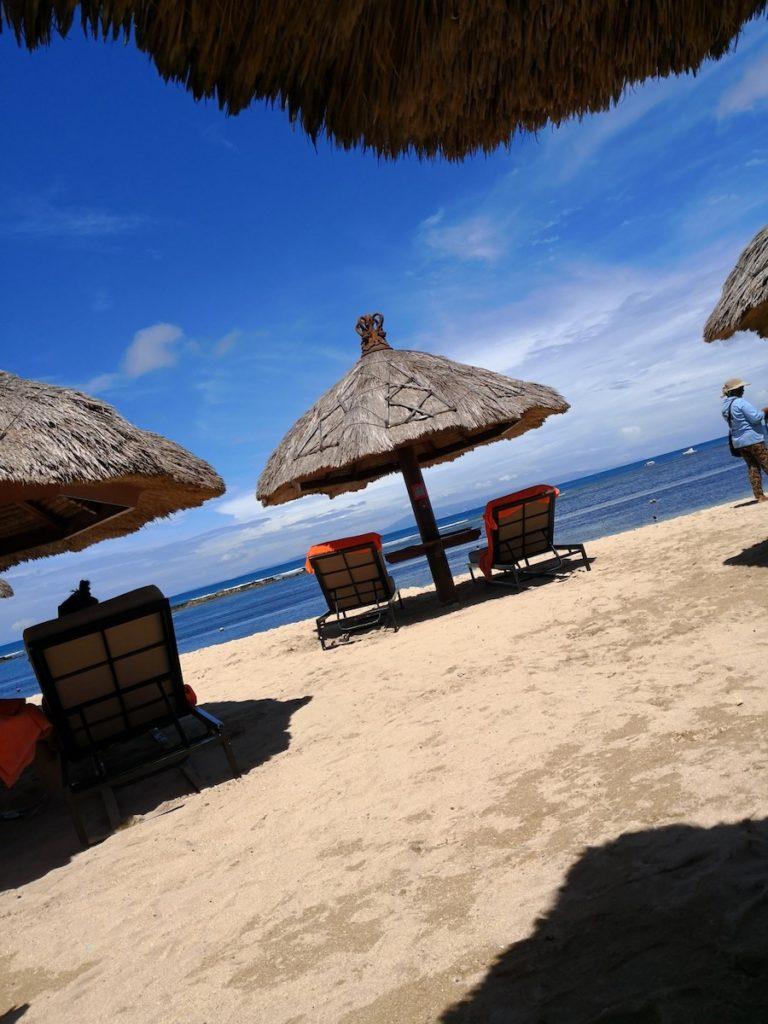 バリ島のソフィテルホテルのプライベートビーチでビーチチェアとパラソル